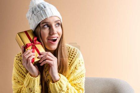 Photo pour Belle femme excitée en pull jaune et chapeau tenant boîte cadeau tout en étant assis dans un fauteuil, isolé sur beige - image libre de droit