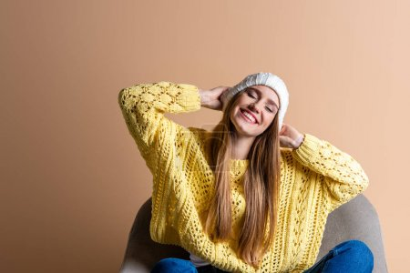 attractive smiling woman in yellow sweater and hat sitting in armchair on beige