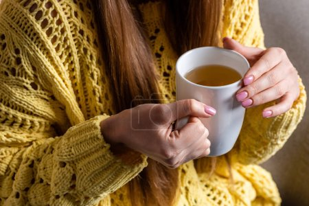 Photo for Cropped view of woman in yellow sweater holding cup of tea - Royalty Free Image