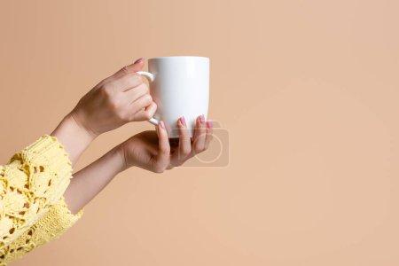 Photo pour Vue partielle d'une femme en chandail jaune tenant une tasse de café, isolée sur beige - image libre de droit