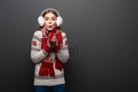 Photo pour Femme surprise en chandail de Noël, écharpe, mitaines et protecteurs d'oreilles, isolée sur gris - image libre de droit