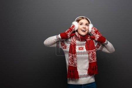 Photo pour Belle femme excitée en chandail de Noël, écharpe, mitaines et protège-oreilles, isolée sur gris - image libre de droit