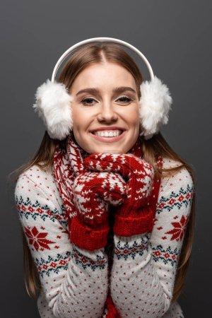 Photo pour Belle femme souriante en chandail de Noël, écharpe, mitaines et protecteurs des oreilles, isolés sur gris - image libre de droit