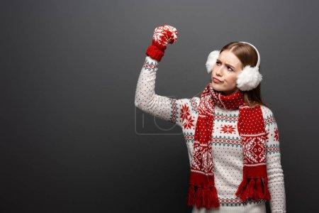 Photo pour Femme sceptique en gestation dans un chandail de Noël, une écharpe, des mitaines et des protecteurs d'oreilles isolés sur gris - image libre de droit