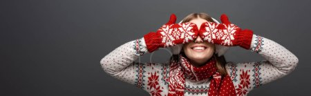 Photo for Panoramic shot of beautiful smiling girl in christmas sweater, scarf, mittens and earmuffs closing eyes, isolated on grey - Royalty Free Image