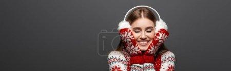 Photo pour Photo panoramique d'une jolie fille aux yeux fermés en chandail de Noël, écharpe, mitaines et protecteurs d'oreilles, isolée sur gris - image libre de droit