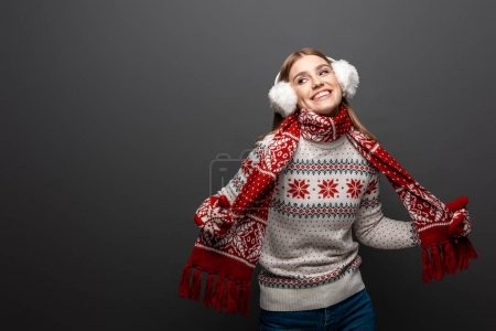 Photo for Attractive smiling woman in christmas sweater, scarf, mittens and earmuffs, isolated on grey - Royalty Free Image