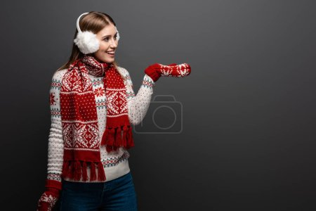 Photo for Happy woman in christmas sweater, scarf, mittens and earmuffs showing something, isolated on grey - Royalty Free Image
