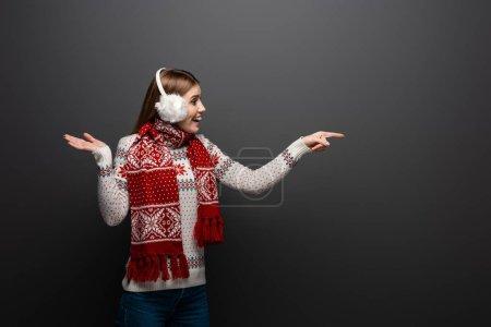 Photo pour Femme excitée en chandail de Noël, écharpe et protecteur des oreilles pointant vers quelque chose, isolée sur grise - image libre de droit