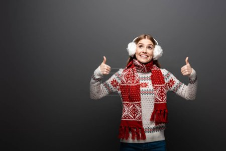 Photo for Happy girl in christmas sweater, scarf and earmuffs winking and showing thumbs up, isolated on grey - Royalty Free Image
