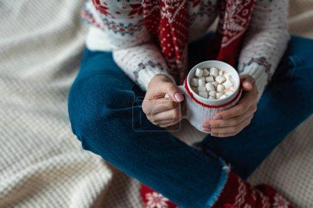 Photo pour Vue recadrée de la femme en pull chaud tenant tasse de cacao avec guimauve et assis sur la couverture - image libre de droit