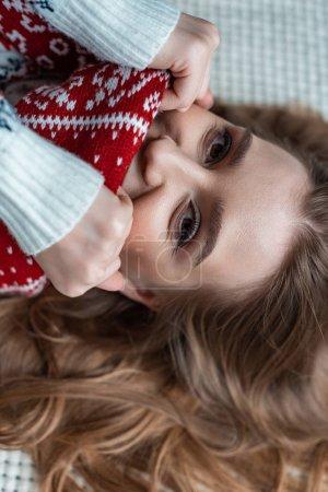 Foto de Mujer atractiva en sudor caliente y bufanda tumbada en la manta - Imagen libre de derechos