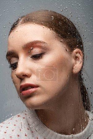 Photo pour Belle femme solitaire sur fond gris, au-delà du verre mouillé avec des gouttes - image libre de droit