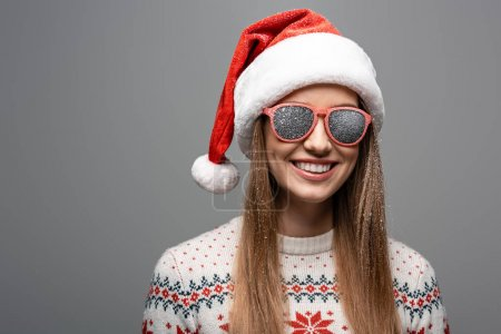 Photo for Beautiful happy woman in christmas sweater, santa hat and sunglasses, isolated on grey - Royalty Free Image