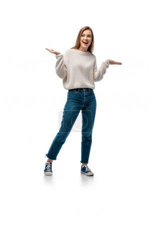 attraktive aufgeregte Frau in Jeans und weißem Pullover, die mit Achselzucken-Geste posiert, isoliert auf weißem Gestus