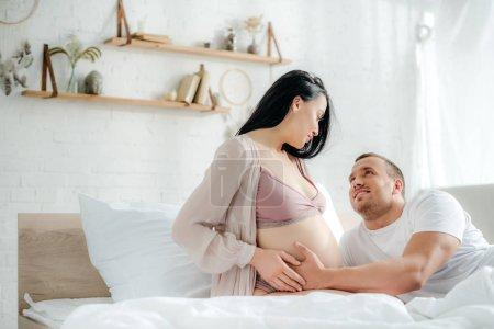 Photo pour Un mari souriant touchant le ventre de sa femme enceinte au lit - image libre de droit