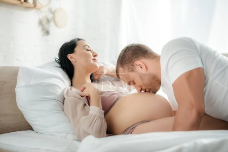 Photo for Happy husband hugging and kissing tummy of his smiling pregnant wife in bed - Royalty Free Image