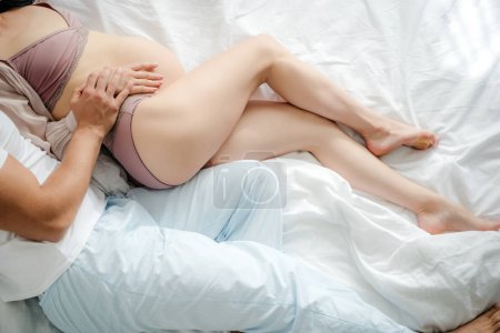 Photo for Top view of husband hugging his pregnant wife while lying on bed - Royalty Free Image