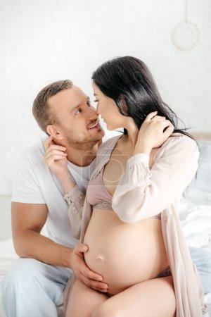 Photo pour Beau mari souriant embrassant et allant embrasser sa femme enceinte au lit - image libre de droit