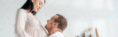 Photo pour Photo panoramique d'un beau mari embrassant sa femme enceinte dans sa chambre à coucher - image libre de droit