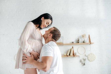 Photo pour Beau mari embrassant sa femme enceinte dans sa chambre - image libre de droit