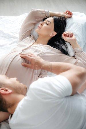 Photo pour Heureux mari embrassant sa belle femme enceinte au lit - image libre de droit