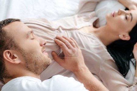 Photo pour Heureux mari embrassant sa femme enceinte au lit - image libre de droit