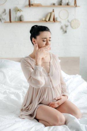 Foto de Chica embarazada atractiva con náuseas mientras se sienta en la cama - Imagen libre de derechos