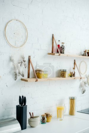 dream catchers and wooden shelves with jars on white brick wall in kitchen