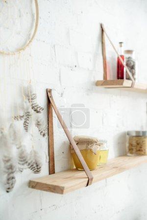 Photo pour Le gros plan du capteur de rêve et des étagères en bois avec bocaux dans la cuisine - image libre de droit