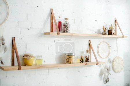 Photo pour Capteurs de rêve et étagères en bois avec bocaux sur mur de brique blanche dans la cuisine - image libre de droit