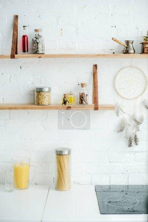 Photo pour Poêle électrique, capteur de rêve et étagères en bois avec bocaux sur mur de brique blanche dans la cuisine - image libre de droit