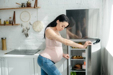 Photo pour Attractive pregnant woman looking into opened fridge in kitchen - image libre de droit