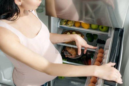 Photo pour Crochet vue d'une fille enceinte pointant vers un réfrigérateur ouvert dans la cuisine - image libre de droit