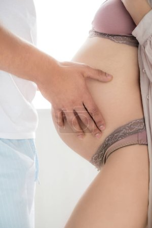 Photo pour Crochet d'un homme tendre touchant le ventre d'une femme enceinte - image libre de droit