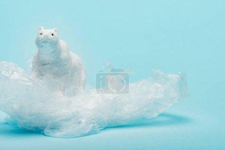 Photo pour Toy polar bear on plastic packet on blue background, animal welfare concept - image libre de droit