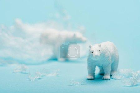 Foto de Osos polares juguetones con basura de polietileno sobre fondo azul, concepto de contaminación ambiental. - Imagen libre de derechos