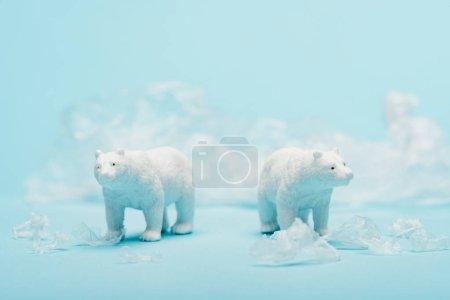 Photo pour Jouet ours polaires avec poubelle en polyéthylène sur fond bleu, concept de bien-être animal - image libre de droit