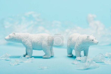 Photo pour Two toy polar bears with polyethylene trash on blue background, animal welfare concept - image libre de droit