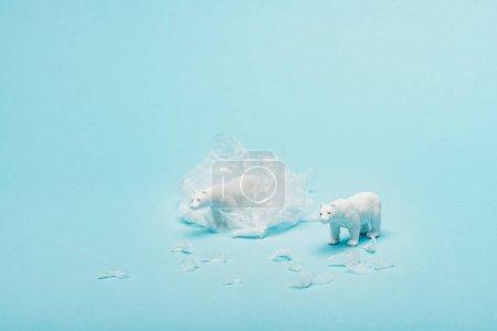 Photo pour Toy polar bears with polyethylene trash on blue background, animal welfare concept - image libre de droit