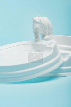 Photo pour Toy polar bear on plastic coffee lids on blue background, animal welfare concept - image libre de droit