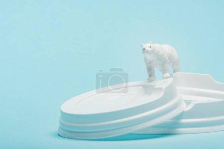 Photo pour Toy polar bear on plastic coffee lids on blue background, ecological problem concept - image libre de droit