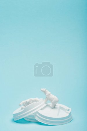 Photo pour Toy polar bears on coffee lids on blue background, animal welfare concept - image libre de droit