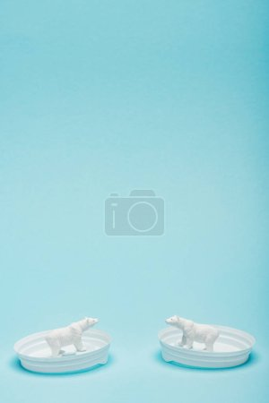 Photo pour Two toy polar bears on coffee lids on blue background with copy space, animal welfare concept - image libre de droit