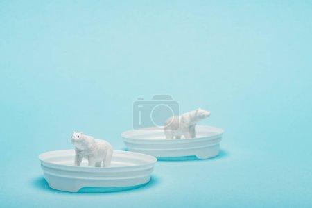 Photo pour Toy polar bears on plastic coffee lids on blue background with copy space, animal welfare concept - image libre de droit