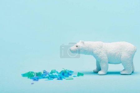Photo pour Jouet ours polaire à côté de pièces en plastique sur fond bleu, concept de bien-être animal - image libre de droit