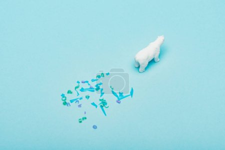 High angle view of of toy polar bear and plastic pieces on blue background, animal welfare concept