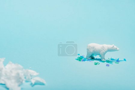 Selective focus of toy polar bear with polyethylene and plastic pieces on blue background, animal welfare concept