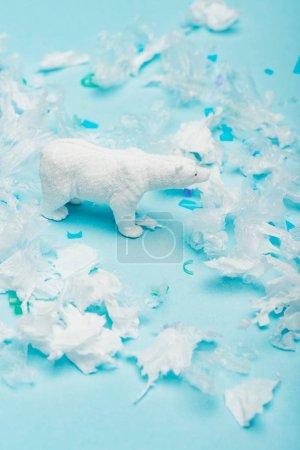Photo pour Ours polaire jouet avec des pièces en polyéthylène et en plastique sur fond bleu, concept de bien-être des animaux - image libre de droit