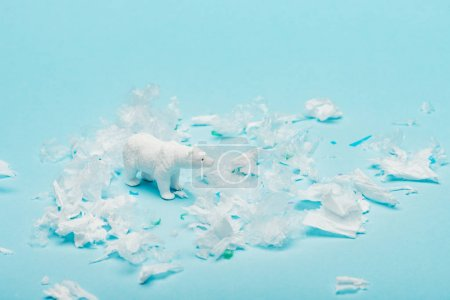 Toy polar bear with polyethylene and plastic garbage on blue background, animal welfare concept